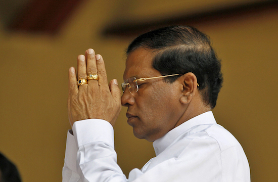 Former Sri Lankan Health Minister and presidential candidate of the common opposition Maithripala Sirisena prays during an event in Colombo, Sri Lanka, Monday, Dec. 1, 2014. Sirisena on Monday signed an agreement with opposition parties, trade unions and professional groups to scrap the country's powerful presidential system and carry out other democratic reforms if he beats incumbent Mahinda Rajapaksa and wins January's presidential election. (AP Photo/Eranga Jayawardena)